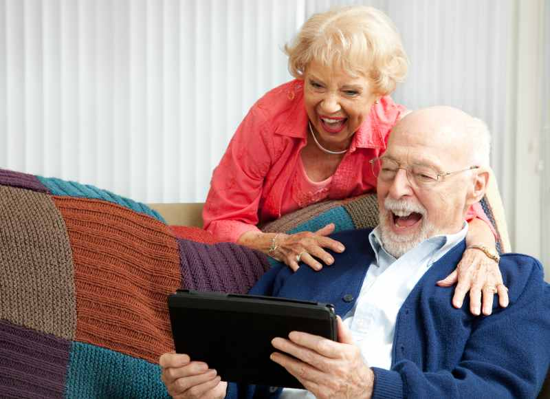 couple laughing at iPad