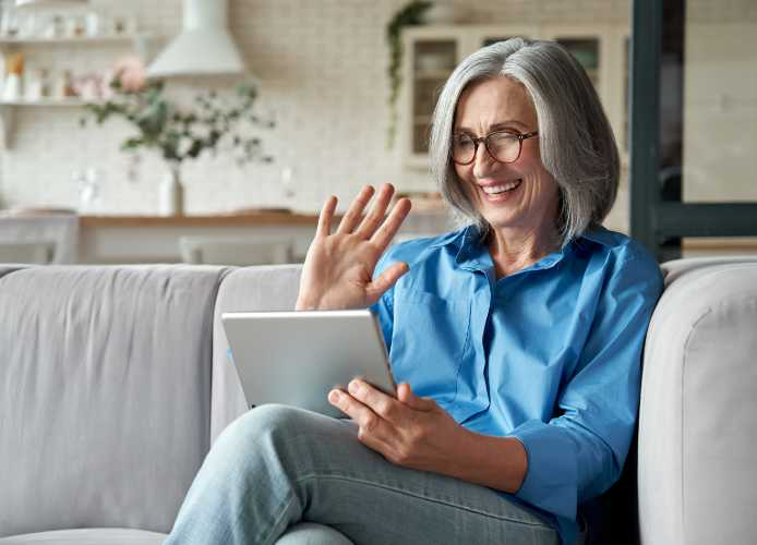 Lady chatting and waving at iPad